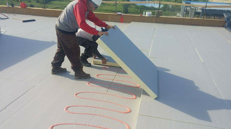 Installing roof insulation with foam adhesive